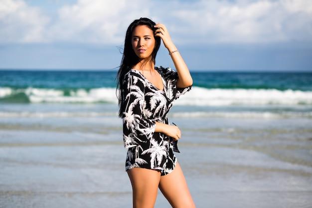 Retrato soleado de estilo de vida de verano de mujer morena elegante posando cerca del océano azul claro