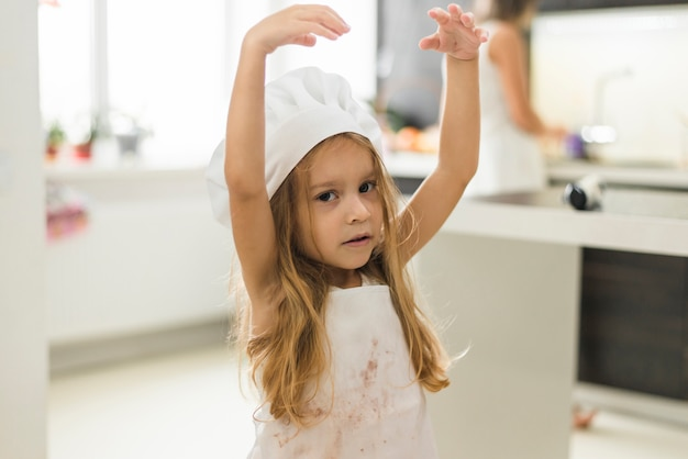 Retrato de un sombrero del cocinero de la muchacha que lleva linda con su brazo levantado