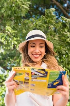 Retrato del sombrero que lleva sonriente de la mujer joven sobre el mapa principal de la lectura