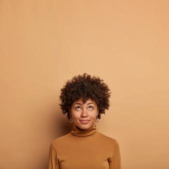Retrato de soñadora joven pensativa concentrada hacia arriba, mira la pancarta promocional, reflexiona sobre algo con expresión alegre, viste ropa casual, posa contra la pared beige.
