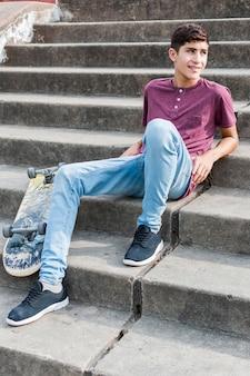 Retrato sonriente de un adolescente que se relaja en escalera con el monopatín