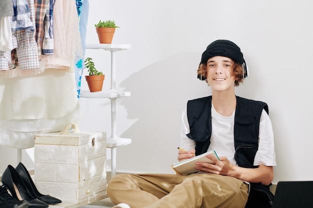 Retrato de sonriente adolescente con sombrero y auriculares sentado en el suelo en casa y escribiendo canciones o dibujando bocetos en el cuaderno