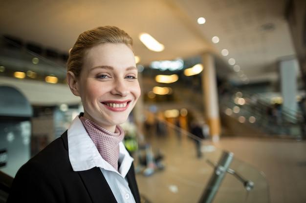 Retrato de sonriente asistente de facturación de la aerolínea en el mostrador
