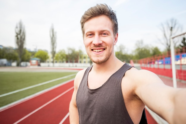 Retrato de sonriente atleta masculino hablando selfie en teléfono móvil