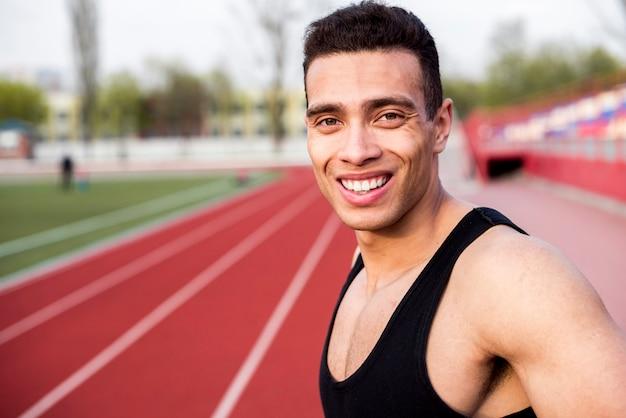 Retrato sonriente de un atleta masculino en la pista de carreras en el estadio