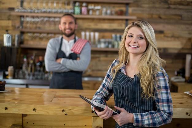 Retrato de sonriente camarera de pie con tableta digital