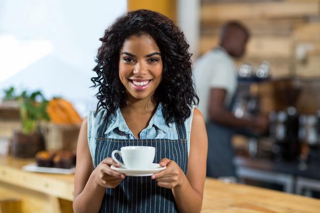 Retrato de sonriente camarera de pie con una taza de café