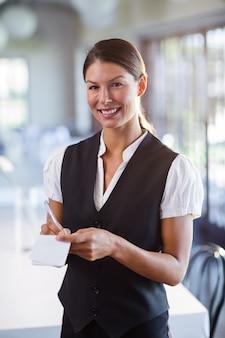 Retrato de sonriente camarera tomando orden