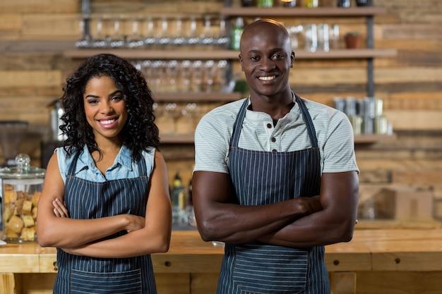 Retrato de sonriente camarero y camarera de pie con los brazos cruzados en el mostrador