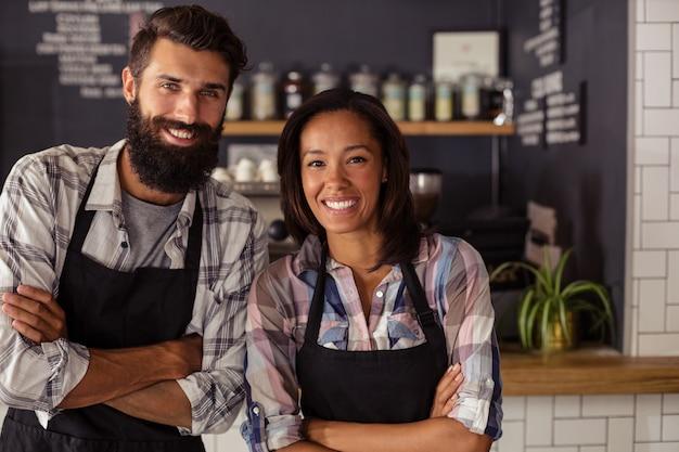 Retrato de sonriente camarero y camarera de pie con los brazos cruzados