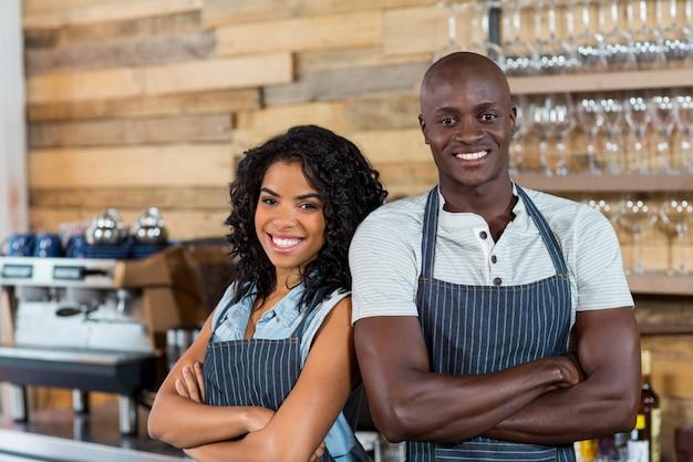 Retrato de sonriente camarero y camarera de pie de espaldas en el mostrador