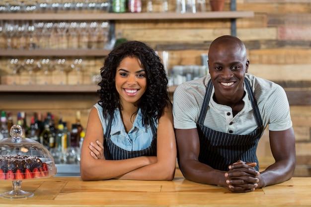 Retrato de sonriente camarero y camarera recostada en el mostrador