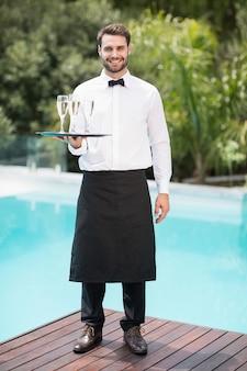Retrato de sonriente camarero llevando flautas de champán