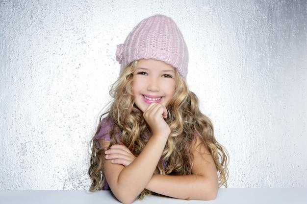 Retrato sonriente del casquillo del rosa del invierno de la niña del gesto