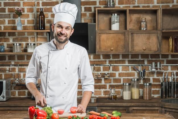 Retrato de sonriente chef hombre de pie detrás de la cocina contra verduras de corte