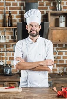 Retrato de sonriente chef masculino confía en pie detrás del mostrador de la cocina