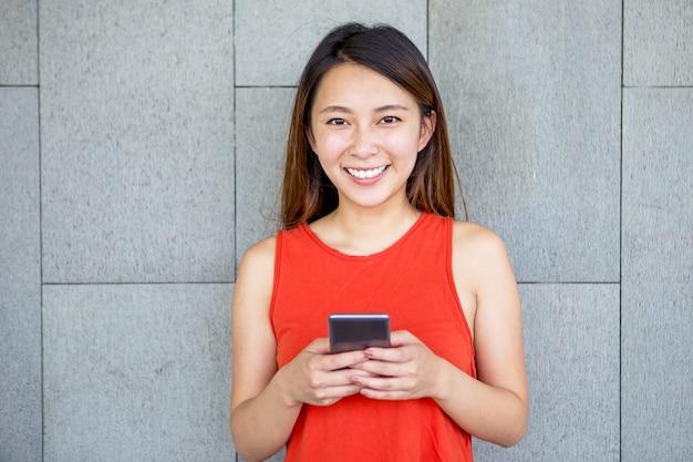 Retrato de sonriente chica asiática con teléfono móvil