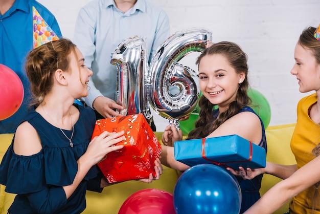 Retrato sonriente de la cumpleañera con el globo de la hoja número 16 y regalos