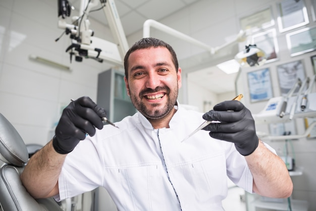 Retrato de sonriente dentista masculino con herramientas dentales