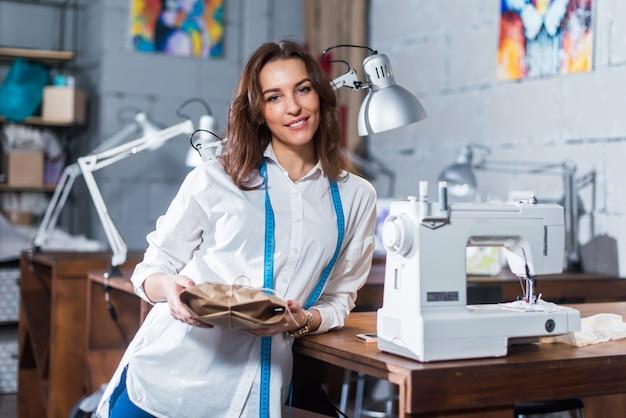 Retrato del sonriente diseñador de moda europeo de pie junto a la máquina de coser sosteniendo un regalo embalado en papel artesanal