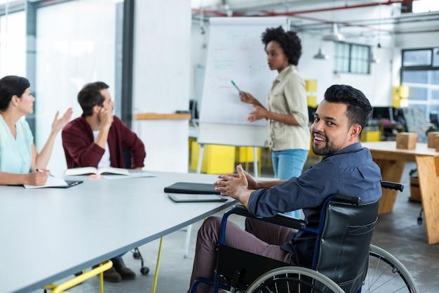 Retrato de sonriente ejecutivo de negocios discapacitados en silla de ruedas en reunión