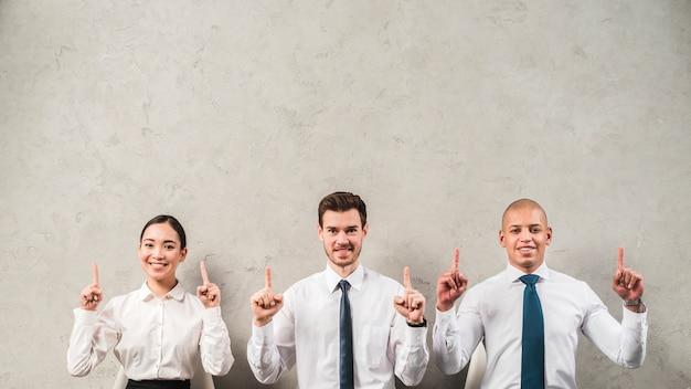 Retrato sonriente de una empresaria y un hombre de negocios que señalan sus dedos hacia arriba contra la pared gris