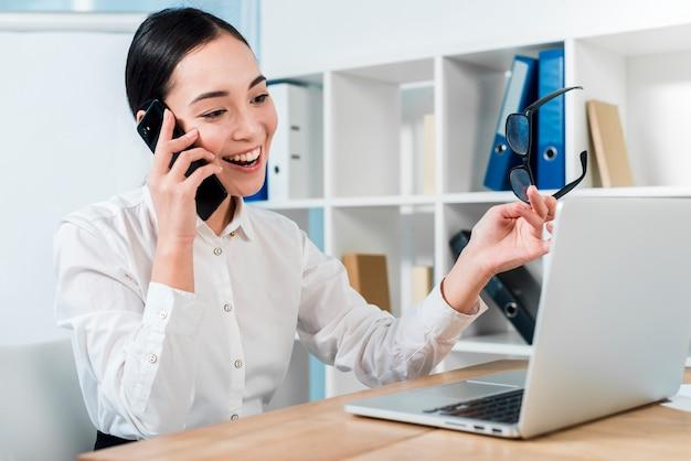 Retrato sonriente de una empresaria joven que habla en el teléfono móvil que mira el ordenador portátil