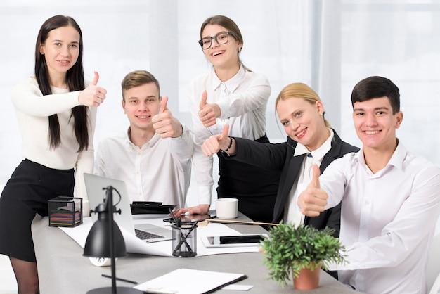 Retrato sonriente de los empresarios que muestran el pulgar encima de la muestra