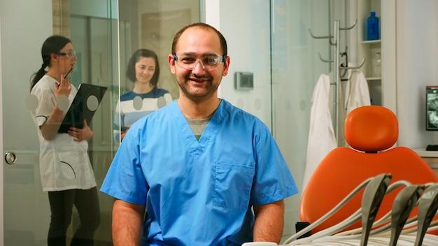 Retrato de sonriente enfermera hombre en consultorio dental mientras el médico pediatra está hablando con el paciente en segundo plano. asistente de estomatólogo mirando a la cámara sentado en una silla en la clínica estomatológica.