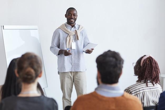 Retrato de sonriente entrenador de negocios afroamericano hablando a la audiencia en la conferencia o seminario educativo, espacio de copia