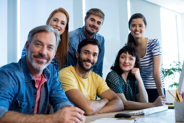 Retrato de sonriente equipo de negocios creativos trabajando juntos en un escritorio en la oficina