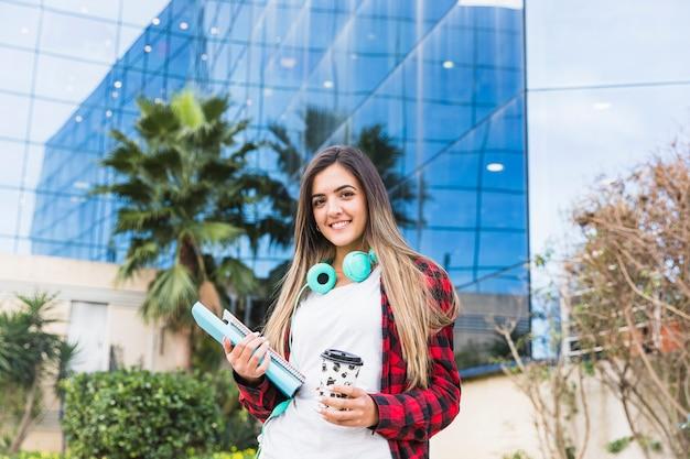 Retrato sonriente de un estudiante joven que sostiene los libros y la taza de café para llevar que se coloca delante del edificio de la universidad