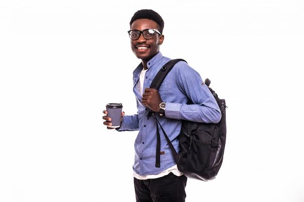 Retrato de un sonriente estudiante universitario masculino afroamericano caminando con café aislado en la pared blanca
