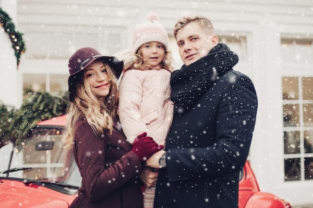 Retrato de sonriente familia de moda posando al aire libre juntos rodeados de nieve y abeto