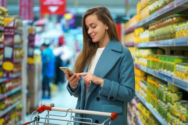 Retrato de una sonriente feliz atractiva joven comprador con carro en el pasillo de la tienda con la lista de compras en el teléfono inteligente durante la compra de alimentos