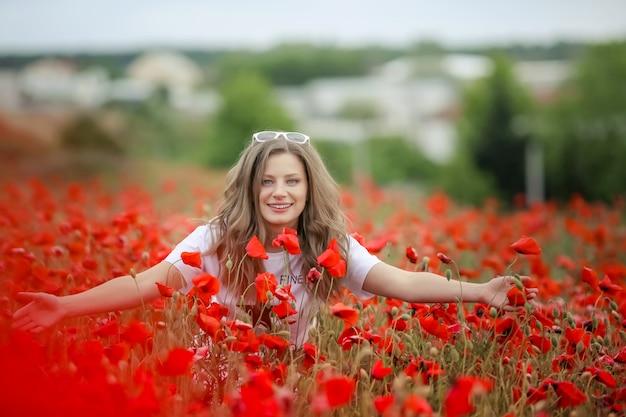 El retrato sonriente feliz hermoso de la muchacha adolescente con las flores rojas en la cabeza que goza en amapolas coloca el fondo de la naturaleza. maquillaje y peinado rizado. estilo de vida.