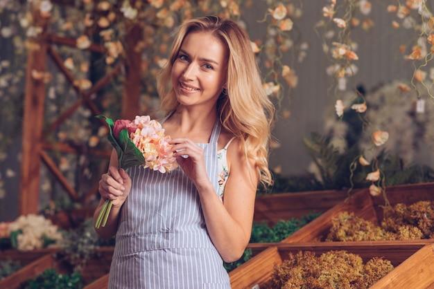 Retrato de sonriente florista mujer rubia con ramo de flores en la mano