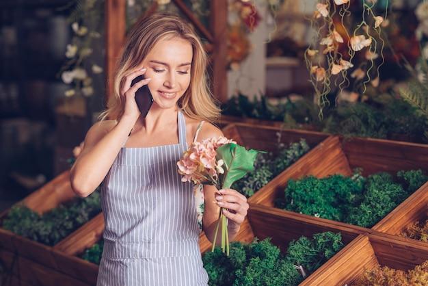 Retrato sonriente de un florista rosa hortensia en la mano hablando por teléfono móvil