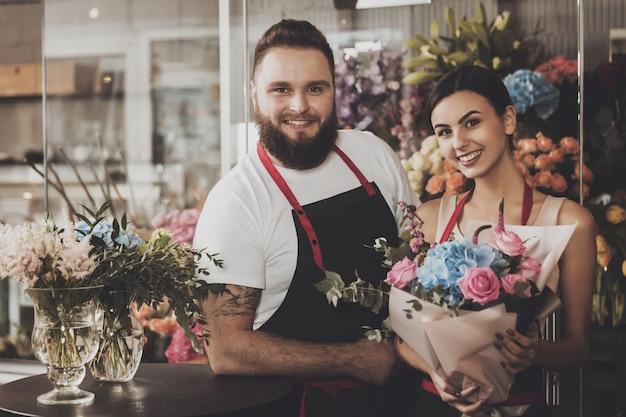 Retrato de sonriente floristas hombre y mujer