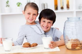 Retrato de sonriente hermano y hermana comiendo galletas