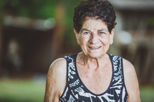 Retrato de sonriente hermosa anciana al aire libre