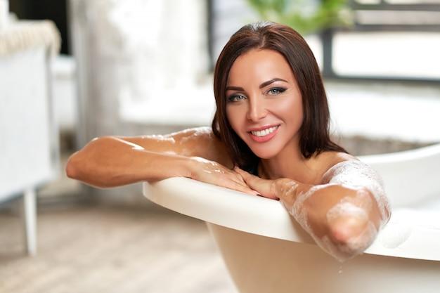 Retrato sonriente hermosa mujer relajante en el baño