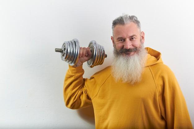 Retrato de sonriente hombre barbudo maduro con mancuernas en casa