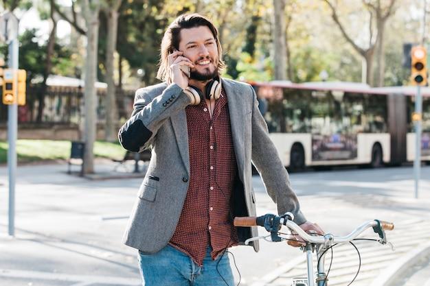 Retrato sonriente de un hombre hermoso que habla en el teléfono móvil que se coloca con la bicicleta
