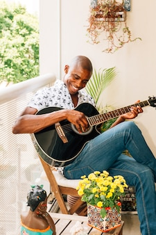 Retrato sonriente de un hombre joven africano que se sienta en la silla que toca la guitarra en el balcón