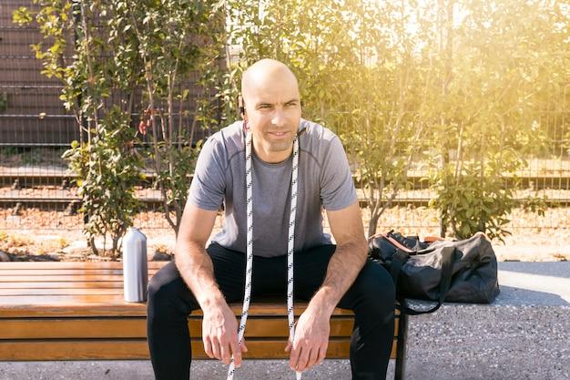 Retrato sonriente de un hombre joven con la cuerda alrededor de su cuello que se sienta en banco en el parque