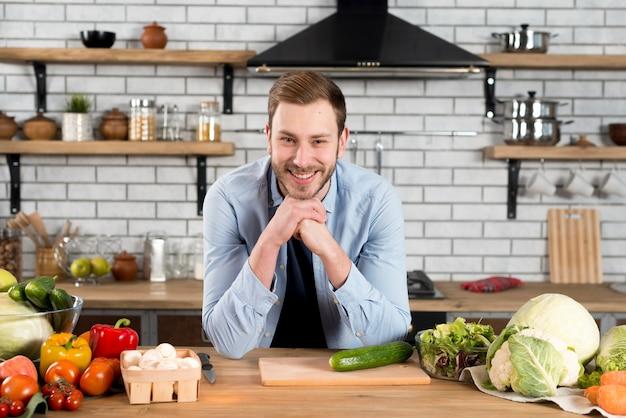 Retrato sonriente de un hombre joven que se coloca detrás de la tabla en la cocina