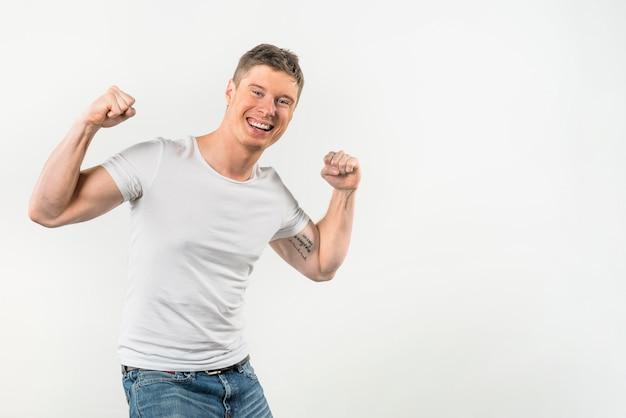 Retrato sonriente de un hombre joven que dobla sus músculos contra el fondo blanco