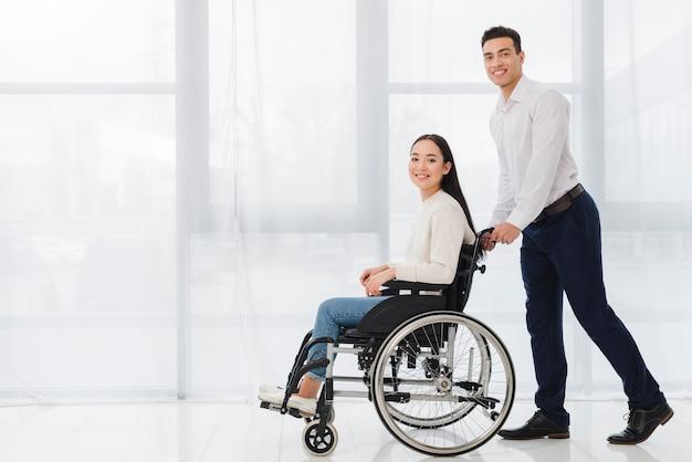 Retrato sonriente de un hombre joven que empuja a la mujer discapacitada que se sienta en la silla de ruedas que mira la cámara