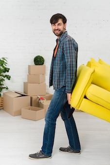 Retrato sonriente de un hombre joven que levanta el sofá amarillo en casa nueva